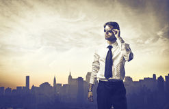 Urban fashion. Handsome young businessman with cityscape in the background Royalty Free Stock Images