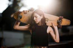 Urban fashionable girl with longboard posing outdoors in the city. Urban fashionable girl with longboard posing outdoors in the city Stock Photos
