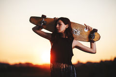 Urban fashionable girl with longboard posing outdoors on the road at sunset. Royalty Free Stock Photos