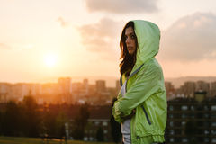 Urban female athlete crossing arms on sunset and city background Royalty Free Stock Image