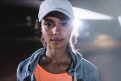 Urban female runner in city at night. Female in sportswear and cap standing outdoors and looking at camera Stock Photos