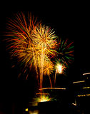 Urban firework celebration on lighted roof tops Stock Images