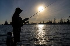 Urban fishing concept. Silhouette of fisherman on industrial seaport city background.  royalty free stock photo