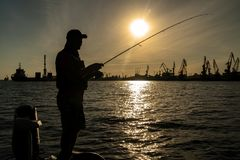 Urban fishing concept. Silhouette of fisherman on industrial seaport city background.  stock photography