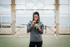 Urban fitness woman drinking detox smoothie on workout rest stock photo