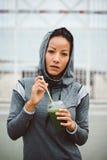 Urban fitness woman drinking detox smoothie on workout rest stock photos