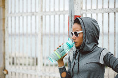 Urban fitness woman drinking water on workout rest Stock Photography