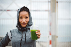 Urban fitness woman holding detox smoothie drink on workout rest. Successful urban sporty woman taking a rest for drinking nutritive detox smoothie. Fitness Stock Photography