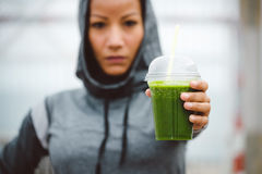 Urban fitness woman showing detox smoothie cup on workout rest Royalty Free Stock Images