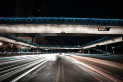 Urban footbridge and road intersection of night scene. Intersection of urban footbridge and highway auto with light trails of night scene Royalty Free Stock Images