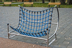 Urban furniture for children 6. Furniture for children's amusement parks. Bank that mimic hammock, with blue ropes and stainless steel metal frame Stock Photos