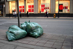 Urban Garbage. Garbage bags on the curb ready for pickup down town Royalty Free Stock Photography