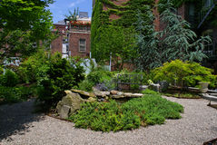 Urban garden. A rock pond and bench located in lush colorful private urban garden Stock Photos