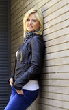 Urban girl. Urban blonde girl dressed in casual clothes - jeans and leather jacket, posing next to a brick wall Royalty Free Stock Images