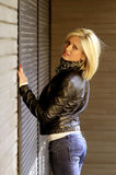 Urban girl. Urban blonde woman dressed in casual clothes - jeans and leather jacket stock photography