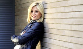 Urban girl. Urban blonde girl dressed in leather jacket, posing next to a brick wall Royalty Free Stock Photography