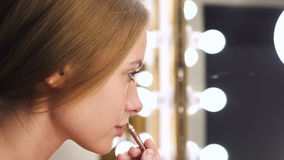 Urban girl applying cosmetic with lip liner. Girl looking in mirror and applying cosmetic with lip pencil before meeting in room. Professional makeup artist stock footage