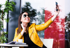 Urban girl in cafe outdoor taking selfie royalty free stock image