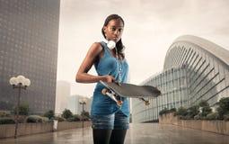 Urban girl. Holding a skateboard in her hands Stock Photos