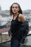 Urban girl posing in a black leather jacket on a rooftop Stock Image