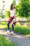 Urban girl riding skateboards on street royalty free stock photos