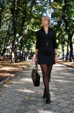 Urban girl in short dress walking in the park Royalty Free Stock Photos