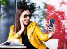 Urban girl sit in cafe outdoor taking selfie Royalty Free Stock Images