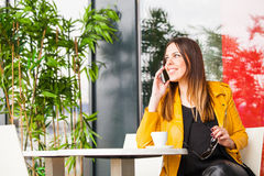 Urban girl sit in cafe talk on smartphone city life concept Royalty Free Stock Photos