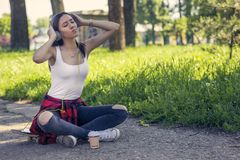 Urban girl sitting on skateboard and listening music. Outdoors, urban lifestyle. Urban girl sitting on skateboard on street and listening music. Outdoors, urban royalty free stock photography