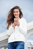 Urban girl with smartphone. Smiling young urban girl with smartphone in blue jeans and white sweater  on stairs summer day in city Stock Photos
