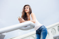 Urban girl with smartphone. Young urban girl with smartphone in blue jeans and white sleeves t-shirt lean on handrail on stairs summer day in city Stock Image