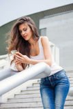 Urban girl with smartphone. Young urban girl with smartphone in blue jeans and white sleeves t-shirt lean on handrail on stairs summer day in city Stock Photos