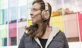 Urban, girl in the street listening to music with headphones on. Her head, she wears a long hair to the wind and winter jacket Stock Photo