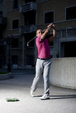 Urban golf. Man playing golf in the city Royalty Free Stock Images