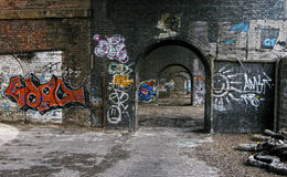 Urban graffiti on a Manchester row of arches. Urban dereliction. An old disused mill in the hart of the city of Manchester England stock photo