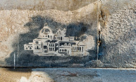 Urban graffiti in Venice, Italy. Painted in the surface of a rough textured weathered wall showing historic buildings in the city stock image