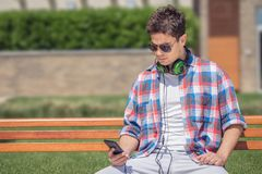 Young man with headphones sitting on bench and using smartphone. Urban guy with headphones holding and looking at his smartphone while sitting on a bench in the Stock Photos
