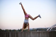 Urban gymnastic exercise. Photo of a young gymnastic girl exercising outdoors. She is standing on her hands, while her legs are in the air Stock Image