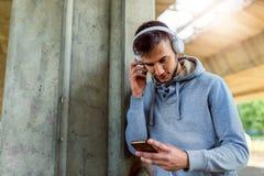 Urban handsome man jogger choosing music on before running Royalty Free Stock Photos