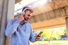 Urban handsome man jogger choosing music on before running Stock Images