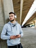 Urban handsome man jogger choosing music on before running Stock Photography