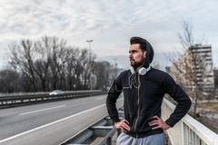 Urban handsome man runner with earphones taking break. On the bridge Royalty Free Stock Image