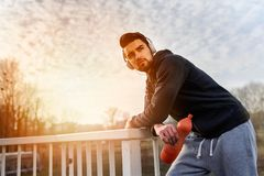 Urban handsome man runner with earphones taking break on the bridge. Jogger man listening music Stock Image