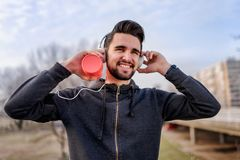 Urban handsome man runner with earphones taking break on the bridge. Jogger man listening music Stock Photo