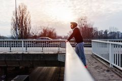 Urban handsome man runner with earphones taking break on the bridge. Jogger man in the sunset Royalty Free Stock Photo