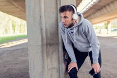 Urban handsome man runner with earphones taking break. Under the bridge Stock Images