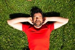 Urban happy sportsman lying on the grass resting Royalty Free Stock Photo
