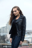 Urban hipster girl posing in a leather jacket on a rooftop.  Royalty Free Stock Image