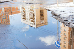 Urban houses and sky reflected in puddle in spring Royalty Free Stock Images