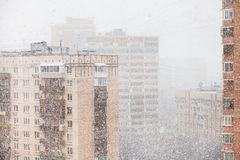 Urban houses and snowfall in city in winter Stock Images